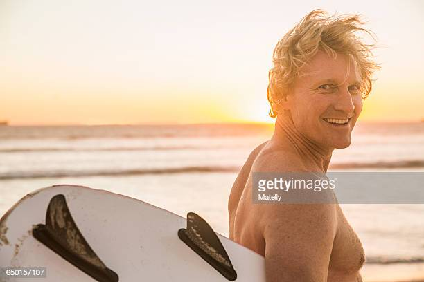 Man on beach carrying surfboard looking over shoulder at camera smiling