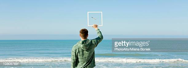 Man on beach holding up picture frame capturing image of gull flying against blue sky