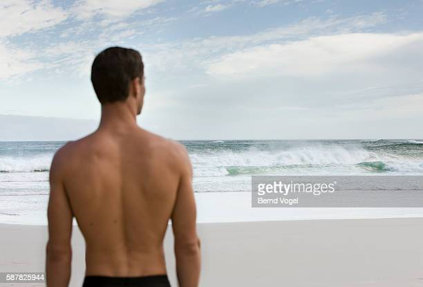 man on beach looking at ocean - halbbekleidet stock-fotos und bilder