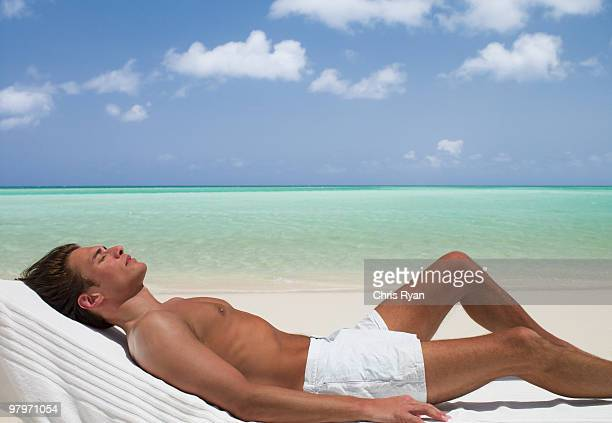 man on beach sunbathing on lounge chair with eyes closed - tumbona fotografías e imágenes de stock