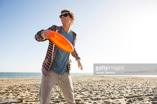 Man on beach tossing frisbee