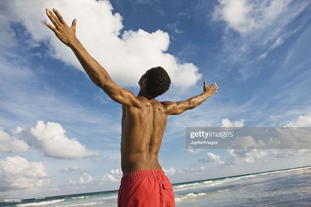 Man on beach with arms outstretched : Stock Photo