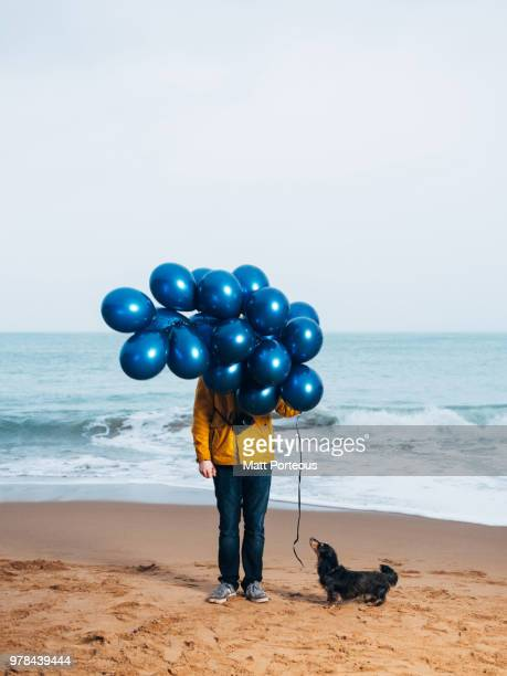 Man on beach with balloons in winter