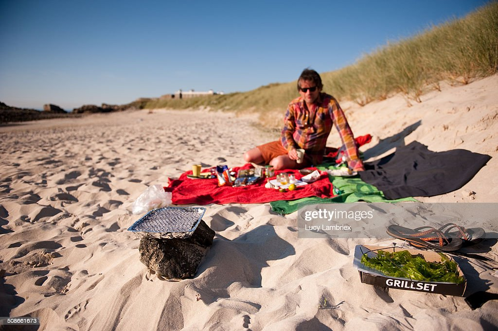 Man on beach with barbecue. Saye beach, Alderney Island. UK.