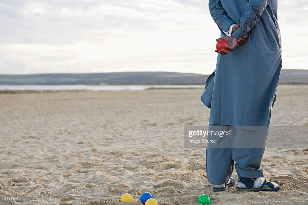 Man on beach with boules set : Stock Photo