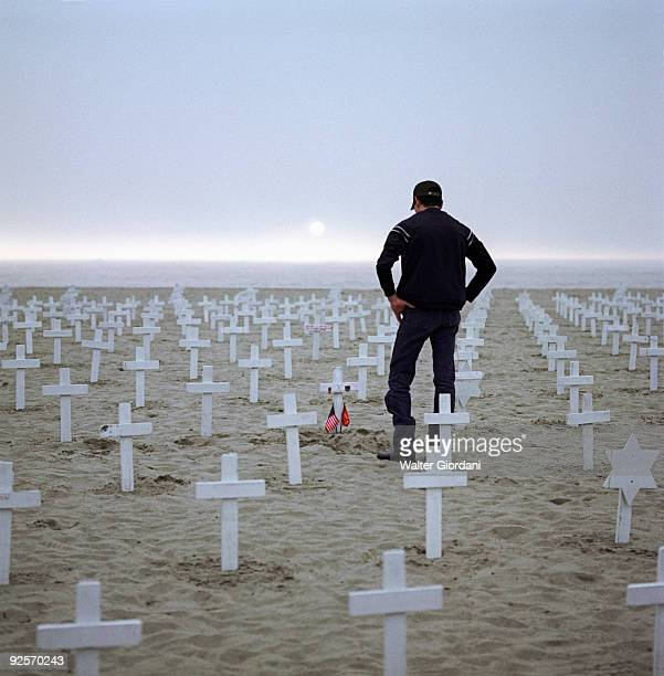 Man on beach with crosses