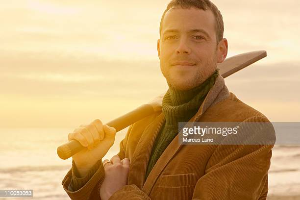 man on beach with old cricket bat - beach cricket stock pictures, royalty-free photos & images