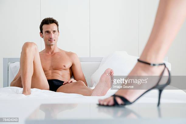 Man on bed and woman in high heels