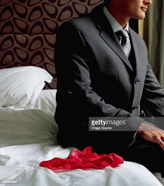 Man on bed next to red knickers