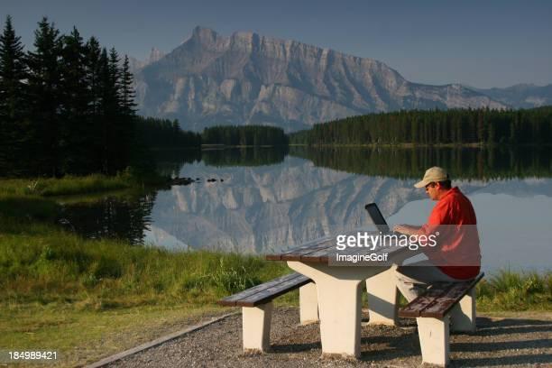 Homme sur un banc entouré par une belle scène travaillant sur un ordinateur portable