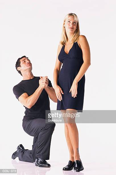 Man on bended knee  woman standing
