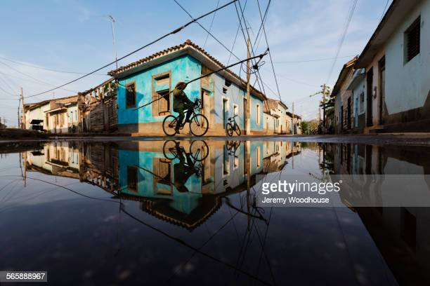 man on bicycle and buildings reflecting in puddle, remedios, santa clara, cuba - キューバ サンタクララ ストックフォトと画像