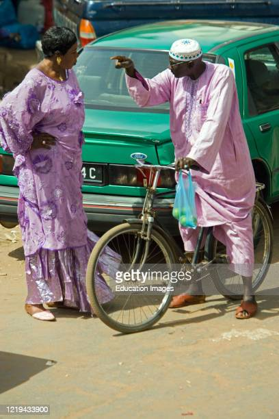 Man on bicycle and standing woman in traditional clothes have vigorous discussion in street Serekunda Market The Gambia.