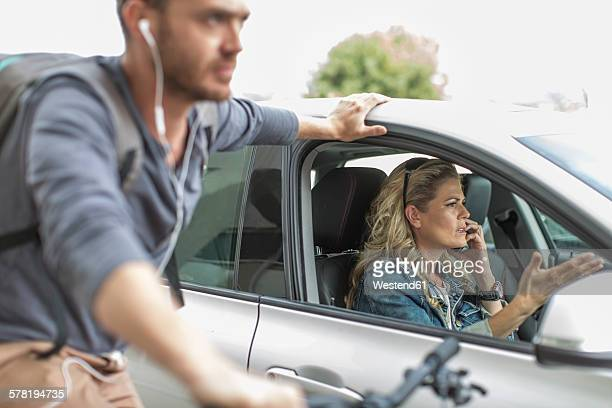 Man on bicycle and woman in car in traffic jam