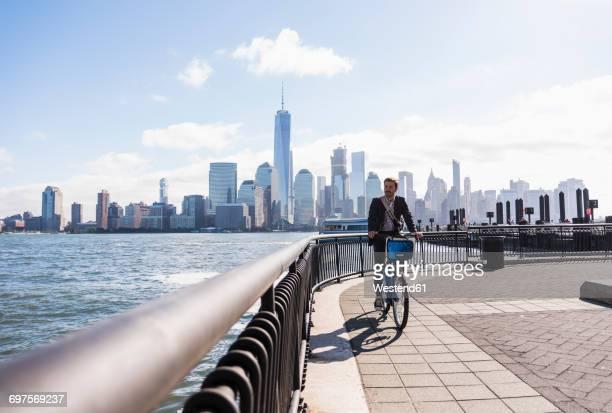 usa, man on bicycle at new jersey waterfront with view to manhattan - wasserrand stock-fotos und bilder