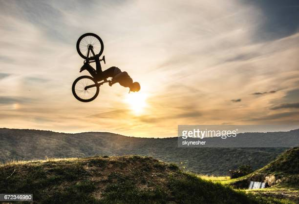 Man on bicycle doing backflip against the sky at sunset.
