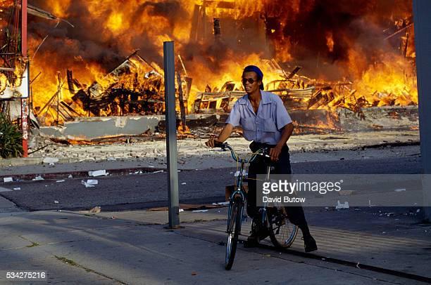 Man on Bicycle near Burning Building