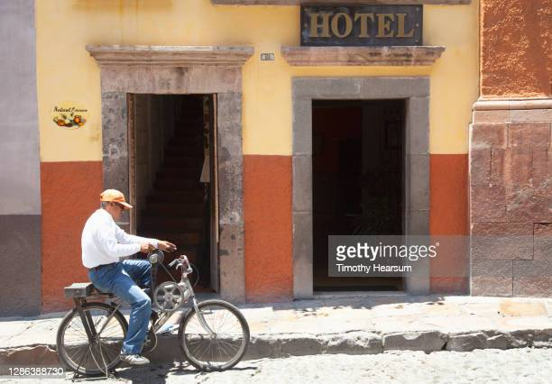 man on bicycle outside a hotel/restaurant - timothy hearsum stock pictures, royalty-free photos & images