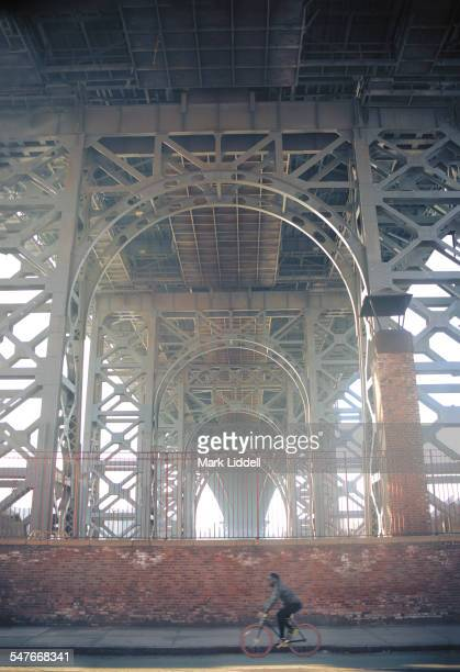 Man on bicycle passing under Williamsburg Bridge
