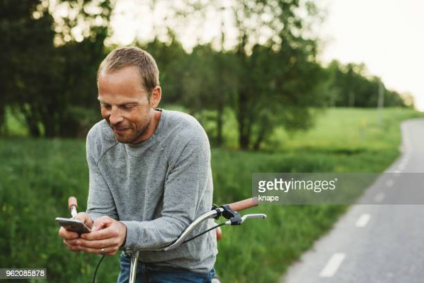 man on bicycle with his smart phone mobile out in rural nature - mid adult men stock pictures, royalty-free photos & images