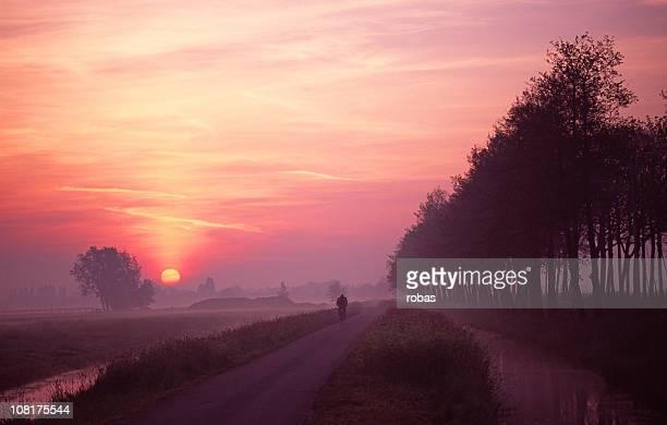 Man on bike during sunset.