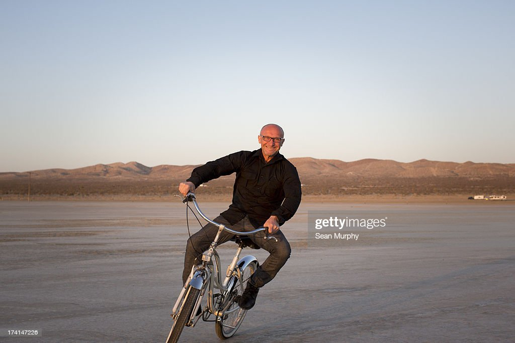 Man on bike in desert : Stock Photo