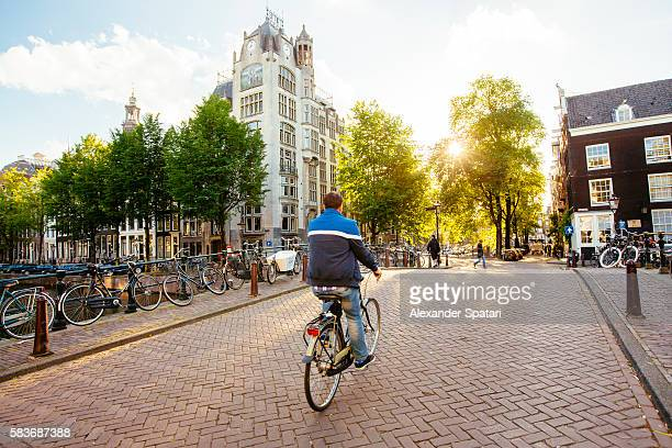Man on bike riding on the streets of Amsterdam at sunset, Netherlands