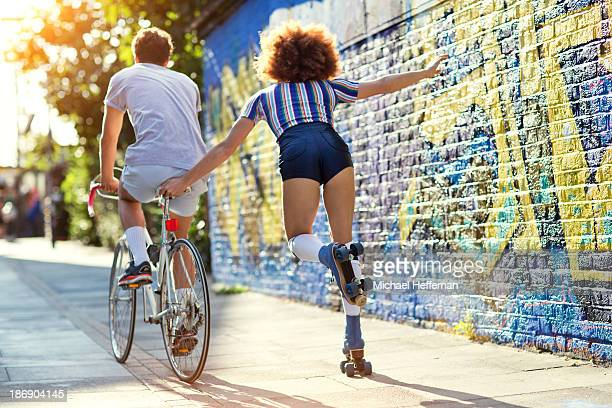 man on bike towing young woman on rollerskates - youth culture stock pictures, royalty-free photos & images