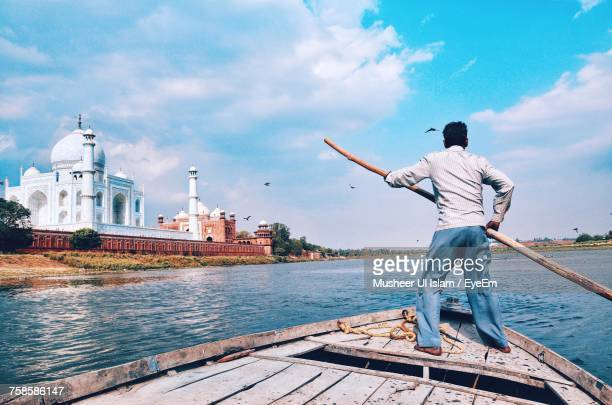man on boat against sky - uttar pradesh stock pictures, royalty-free photos & images