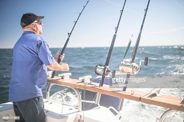 Man on boat deep sea fishing