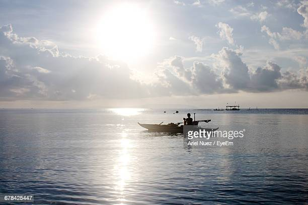 Man On Boat In Sea Against Cloudy Sky