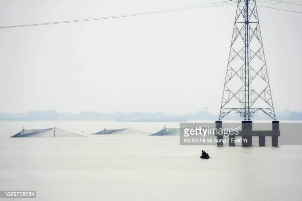 man on boat in sea against sky - ko ko htike aung stock pictures, royalty-free photos & images