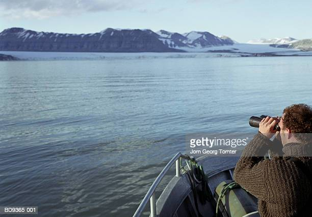 Man on boat looking through binoculars, rear view