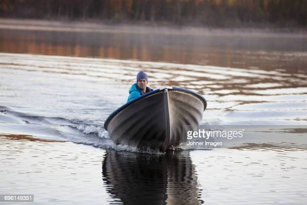man on boat - motorboat stock photos and pictures