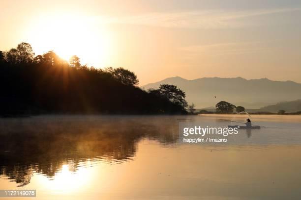 a man on boat rowing in lake, changnyeong, south korea - feuchtgebiet stock-fotos und bilder