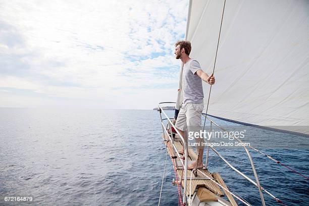 man on bow of sailboat looking out over sea - schiffsbug stock-fotos und bilder