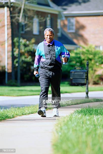 man on brisk walk through neighborhood - alertness stock pictures, royalty-free photos & images
