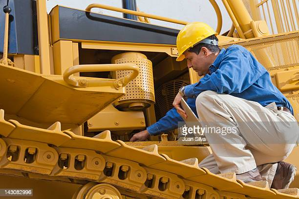 man on bulldozer with tablet looking at engine - baumaschine stock-fotos und bilder