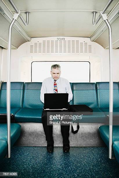 Man on bus with laptop computer