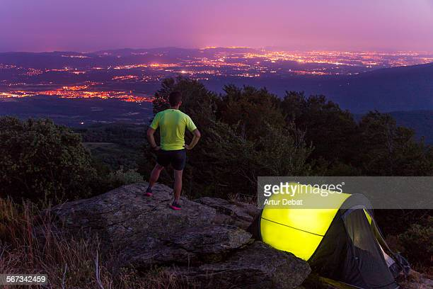 Man on camping tent at night with the city lights.