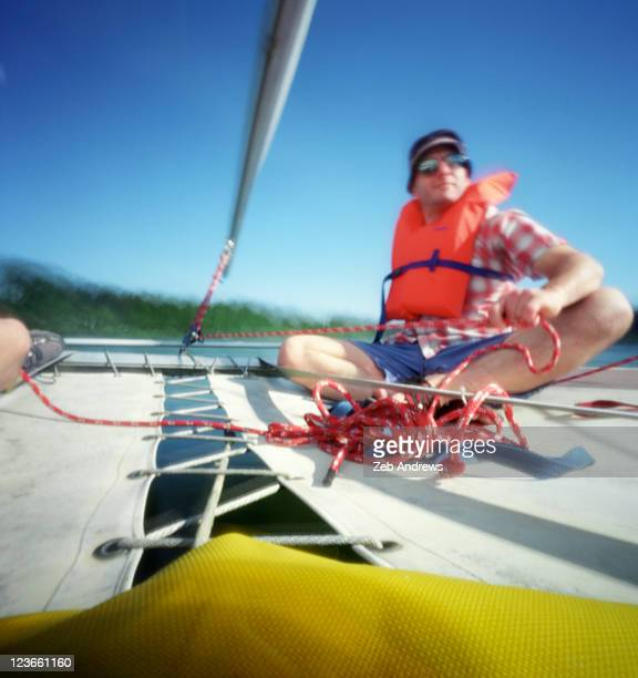 man on catamaran sail boat - willamette river stock photos and pictures