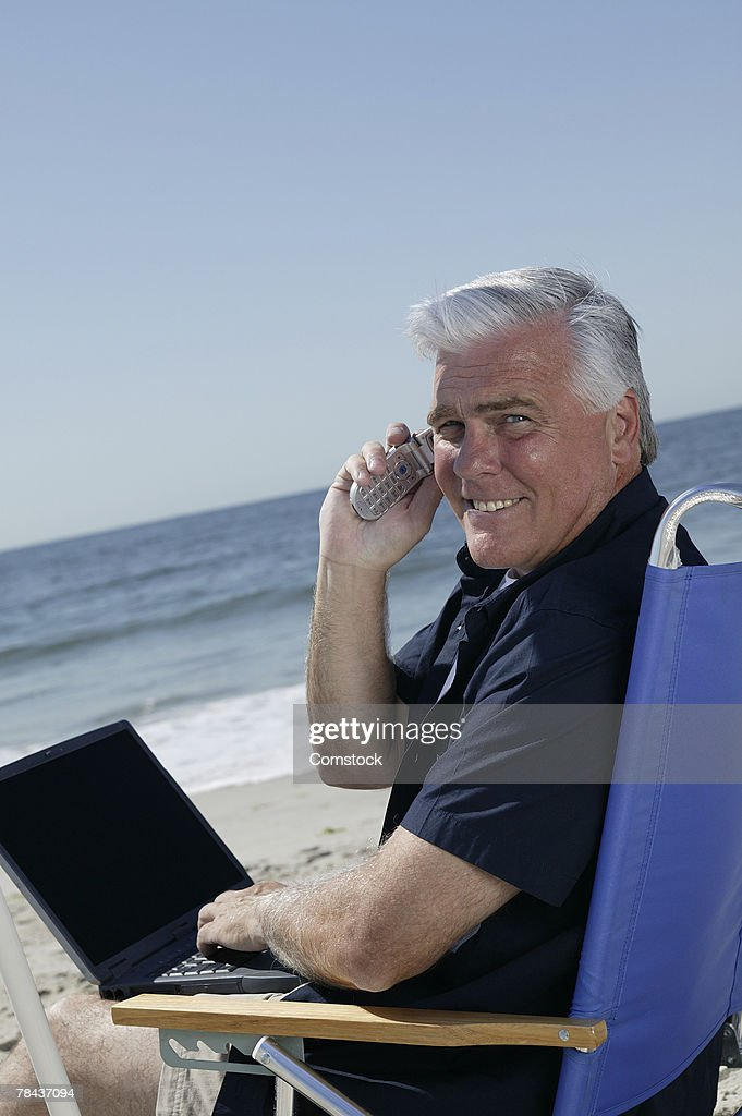 Man on cell phone and using laptop computer at beach : Stockfoto