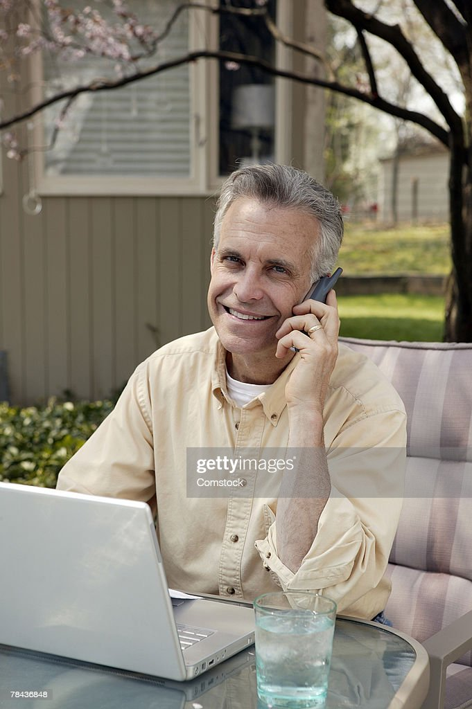 Man on cell phone and using laptop computer in backyard : Stockfoto