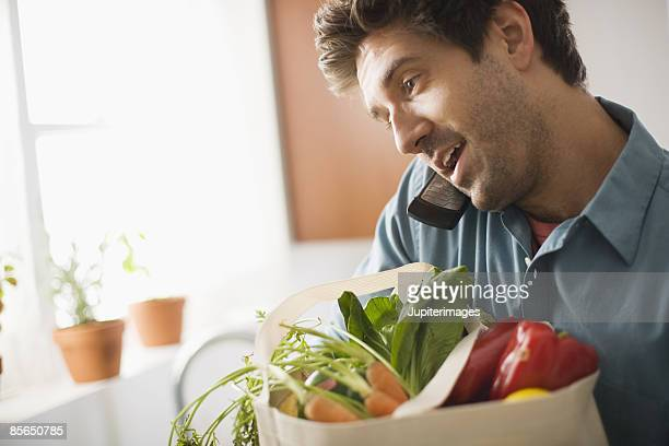 Man on cell phone holding produce in canvas bag