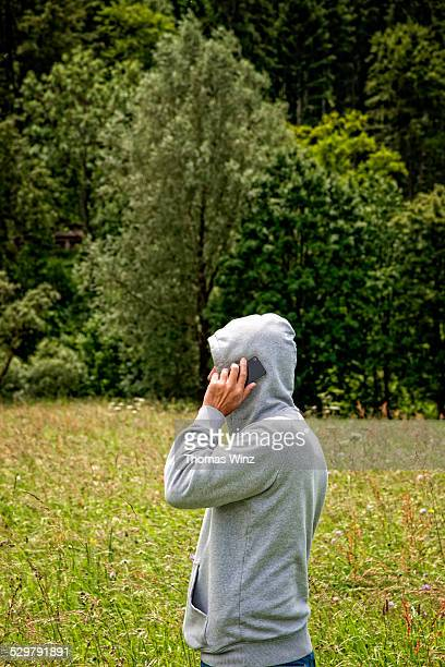 Man on cell phone in a field of grass
