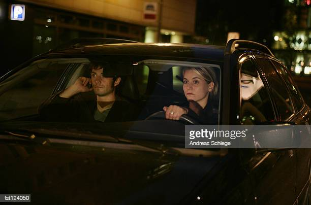Man on cell phone while woman drives a car