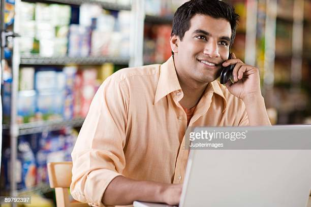 Man on cell phone with laptop