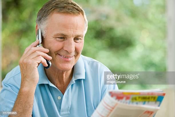 Homme sur téléphone portable avec magazine