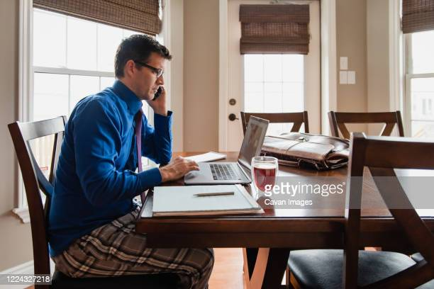 man on cellphone working from home using a computer in pyjama pants. - nightwear stock pictures, royalty-free photos & images