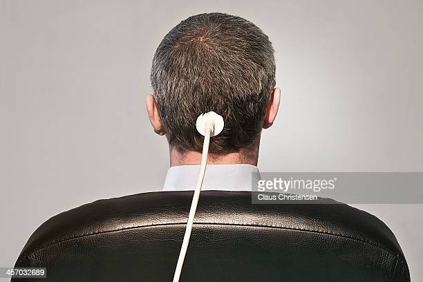 man on chair with cable on head